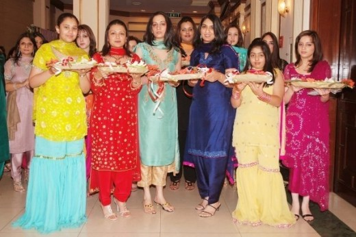 Here we see a throng of girls at a Pakistani mehndi event. Mehndi, Urdu for henna, is a traditional ceremony performed before a Pakistani wedding. Both the bride and the groom are decorated with elaborate body art created out of henna leaves, with th
