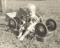 Virginia as a toddler sitting on overturned wagon holding puppy