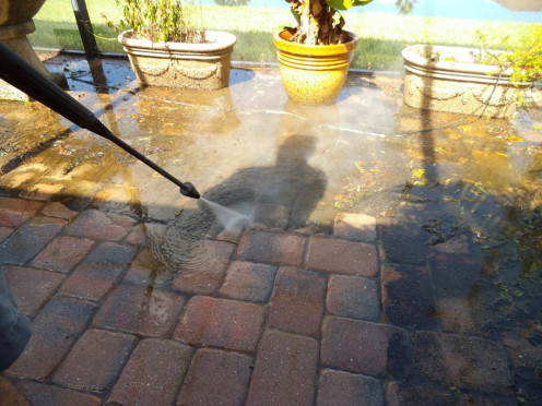 Here's my husband with the pressure washer. Note the area cleaned, compared to the still moldy area.
