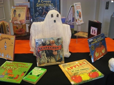 A large prop and colorful background show off a display of holiday books.
