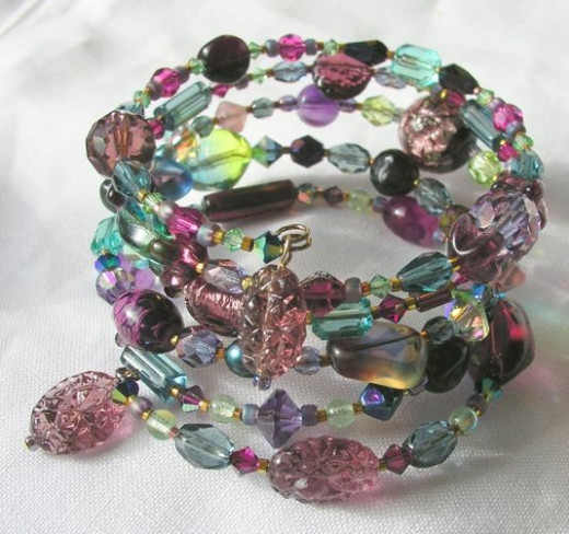 This multi-wrap coil bracelet features a combination of vintage and contemporary glass beads and pressed glass bead dangles in an interesting mix of cool shades.