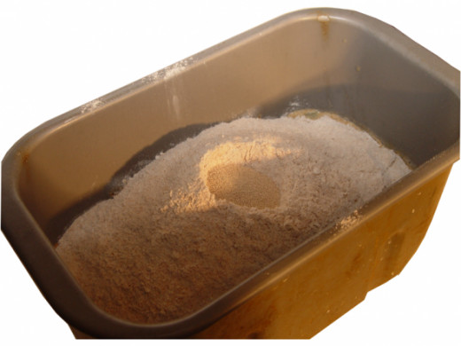 Follow by piling the flour and other dry ingredients, with a small well at top for the yeast.