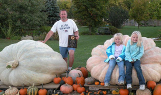 South Dakota farmer Kevin Marsh stands next to his 1,674-pound pumpkin near Parker. To his right, his daughters Maddie and Autumn sit on a 1,536-pound pumpkin he grew