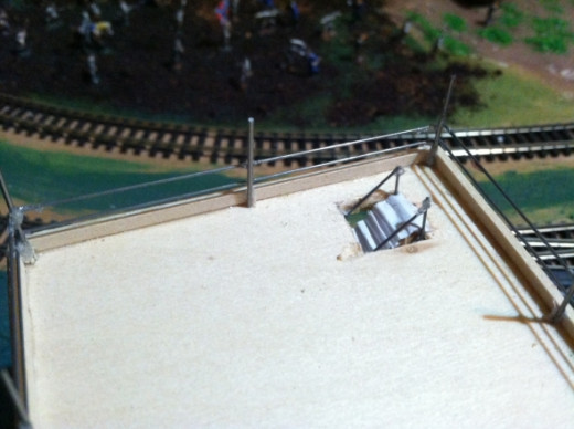 The steps emerging through the platform. To give the edge of the hole a more finished look, attach tiny basswood strips around three sides. Leave the side open where miniature people will enter or exit