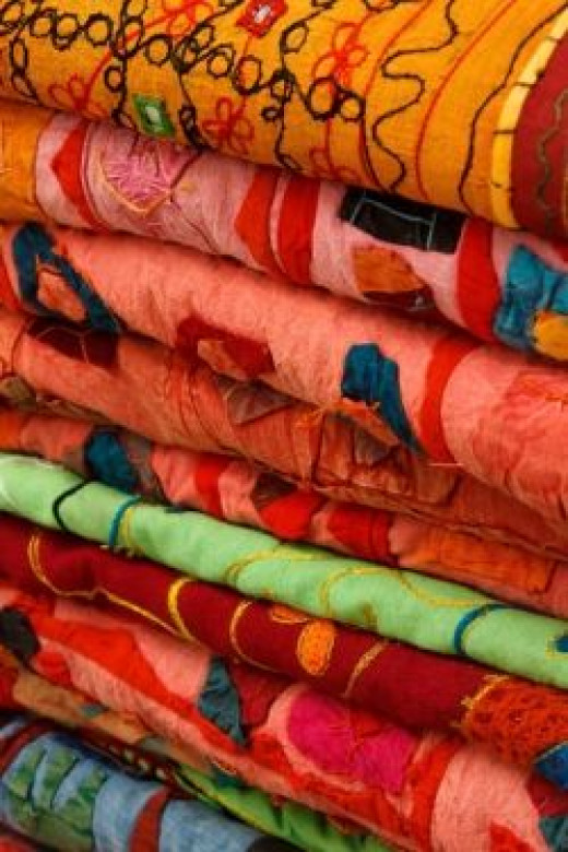 Colorful Fabrics Stacked by Vera Kratochvil at www.publicdomainpictures.net