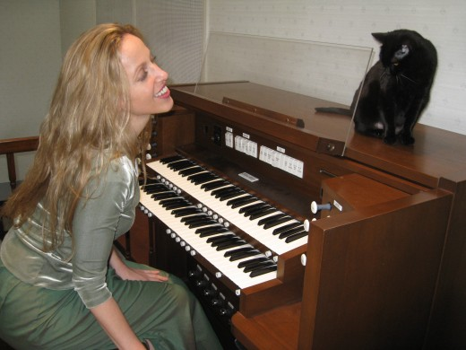 Kristen Lawrence is a classically trained organist who writes Halloween music.  Her little black kitty Molly often joins her for practice time.