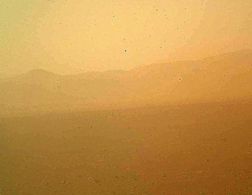 This is the first color photo from Curiosity. It appears fuzzy because of dust on the camera lens but it is exciting to get a view. You can tell why it is called the Red Planet! The rover is in a crater right now and slowly moving towards the edges t