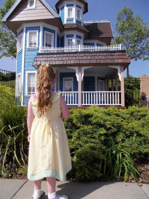 "The ""before"" photo of my daughter in front of a miniature Victorian house."