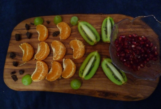 Fruit selection on a wooden platter, kiwis, grapes,clementines and quality chocolate pieces