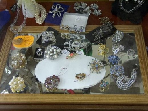 Vintage pins and brooches and other costume jewelry on display