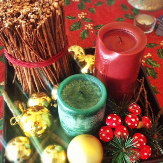 A simple dining table centerpiece created with a wooden tray, cinnamon sticks, candles, ceramic mushrooms and gold ornaments.