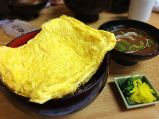 Under this thick blanket of egg omelette lies some broiled eggs over a mound of rice.