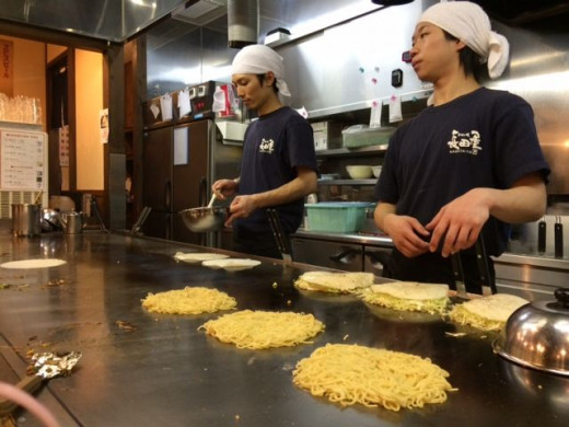 The beginnings of the okonomiyaki. Here are the noodle and flour batter layers being cooked.