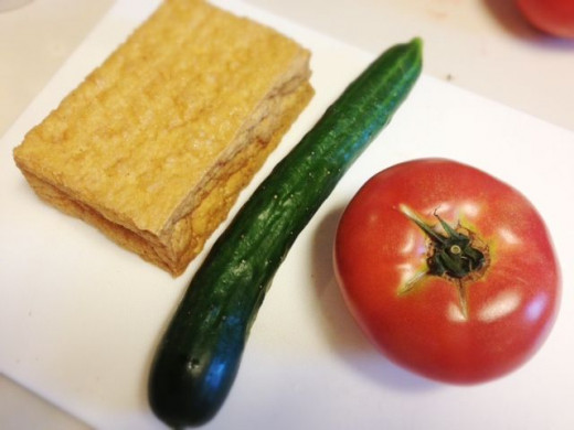 Raw ingredients are aburaage(deep fried tofu), cucumber and a tomato.