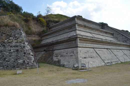 A large structure juts from the hillside with stairs to an overall view
