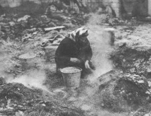 Woman gathering grain in war damaged building