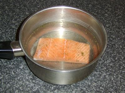 Salmon fillet is seasoned and covered with cold water