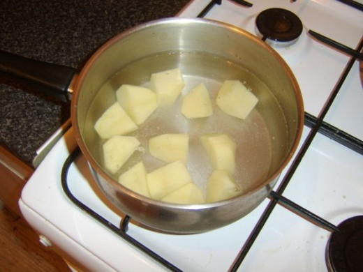 Potatoes are peeled, chopped and added to cold, salted water
