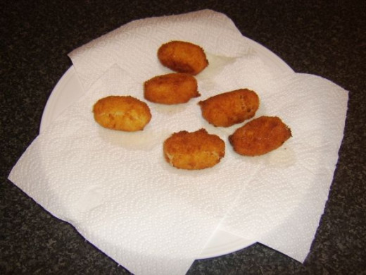 Deep fried potato croquettes are drained on kitchen paper