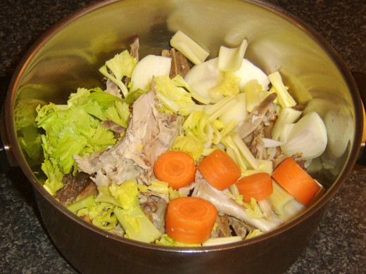 Chopped vegetables and seasonings are added to stock pot with turkey bones