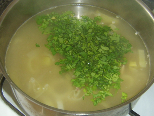 Chopped parsley is added to soup