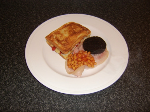Baked beans and black pudding are laid on bacon