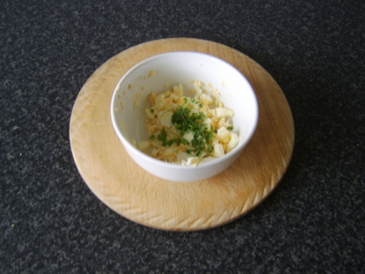 Salad cress is stirred through the mashed egg