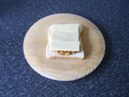 Cheese is laid on top of the baked beans and pickle