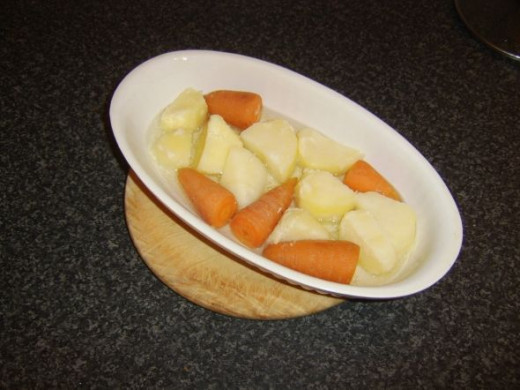 Carrots and potatoes are stirred through the hot duck or goose fat