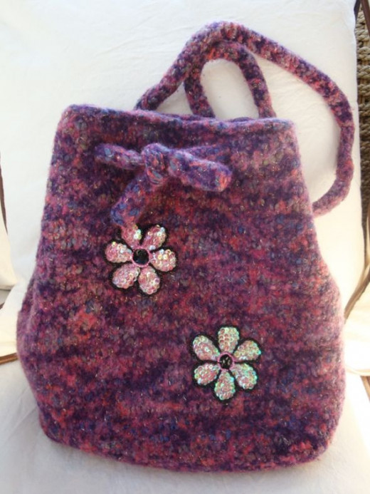 These hobo style purses used 100% wool and have I-cords to carry them around. The same pattern was used to create the black/gray purse, yet each one has a distinct purse-onality. The added bling-bling and appliques made all the difference between cas