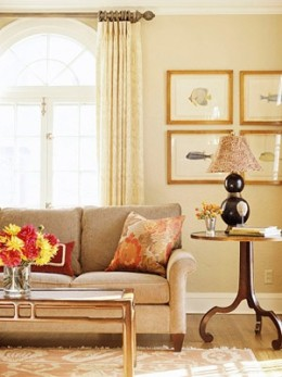 A living room is cozy for family time but retains an air of style for entertaining. Accessories such as a gourd lamp with a feather-covered shade bring panache to the space. To add a subtle beach element, antique hand-painted fish prints hang behind