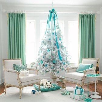 Modern GlamourA petite white fir tree, heavily flocked at the tree lot, makes a big statement in a small room. Flocked trees may be a retro thought but look thoroughly modern when paired with a crisp white-on-white color scheme. Bursts of peacock b
