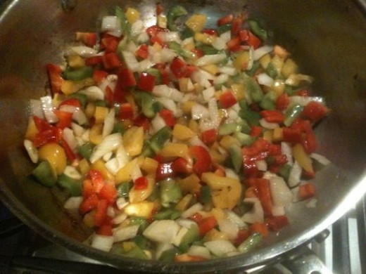 Cooking the vegetables down in the remaining sausage and chicken fat.