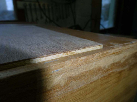 Plywood placed on the bottom of the drawer shows extensive wear at the back.