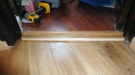 Step up into home office with laminated wood floor using scrap wood to make the door step.