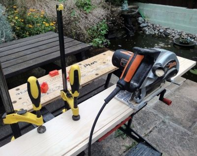 Using clamps and saw guide to cut timber