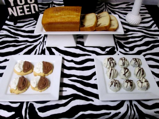 front featurs white marble loaf cake on a double pedestal rectangle platter, 2 square platters with dipped fortune cookies & white chocolate truffles