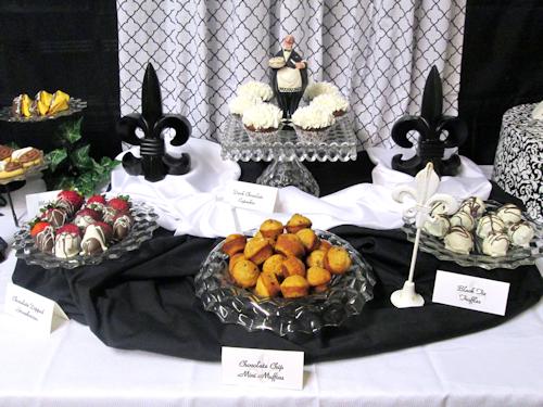 Center -- Elegant Fostoria square cake stand & Maitre'd take residence flanked by 2 fleur de lis, 2 platters on risers, an elegant bowl of muffins.