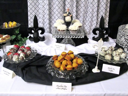 Center -- Elegant Fostoria square cake stand & Maitre'd take residence flanked by 2 fleur de lis, 2 platters on risers, an elegant bowl of muffins.