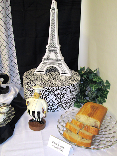 Right- Black and white Eiffel Tower on top of a damask hat box, a jolly French Chef, some greenery  and a white marble cake on a Fosteria platter.