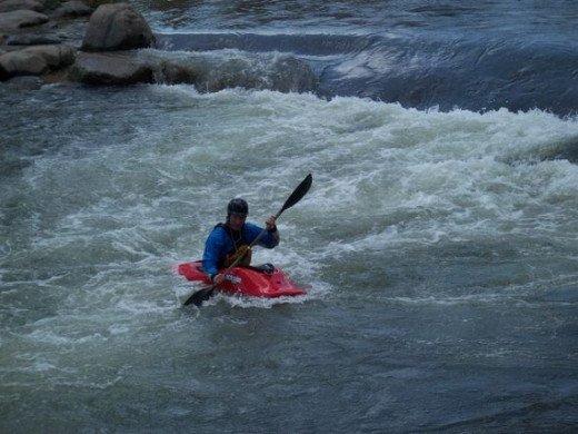 Kayaker playing on the river