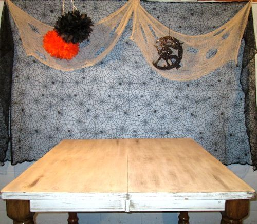 I made the backdrop from a spiderweb design tablecloth, added creepy cloth, hung a couple of vintage tissue balls and a vintage style witch and moon.