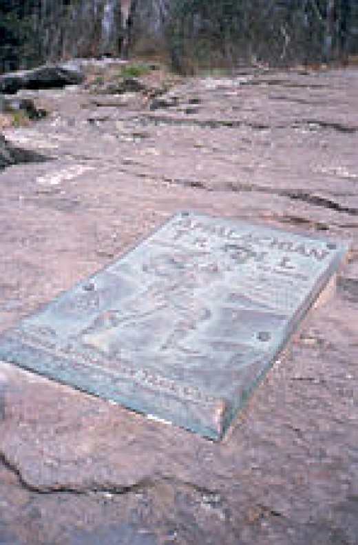 The plaque on Springer Mountain and the first white blaze (upper-left)