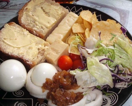 Ploughman's, buttered bread rolls, crisps (potato chips in American), hard boiled eggs, onion rings, salad and tomatoes with green tomato chutney.