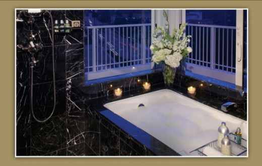 Sunken bathtub is enclosed with black imported Italian marble...you have to light your own candles!
