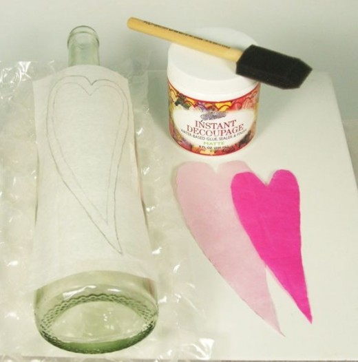 "1. Using a piece of tissue paper the length and width of the bottle place it on the bottle and draw your heart designs. Using two shades of pink tissue cut out two hearts--one 1/2"" larger than the other. Using decoupage paste glue the larger heart an"