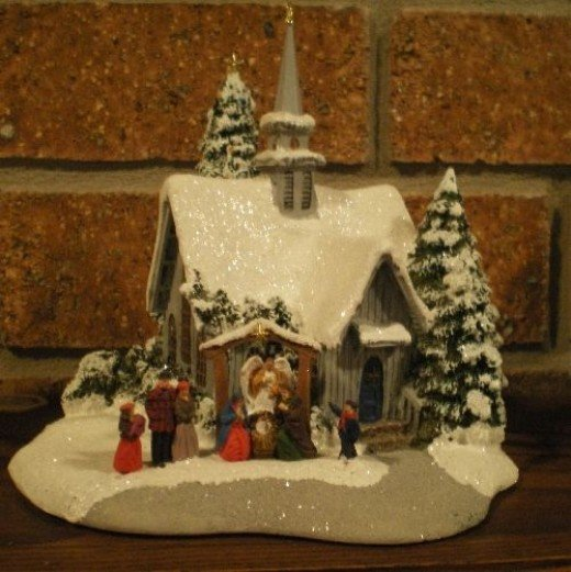 A Thomas Kinkade snow-covered church displaying The Nativity out front
