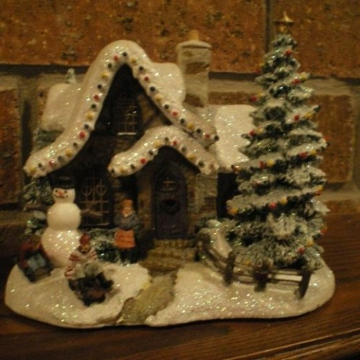 A Thomas Kinkade Christmas home with a snowman in front yard