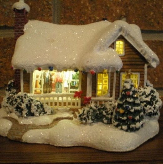 A Thomas Kinkade snow-covered home with a flickering fireplace and people inside
