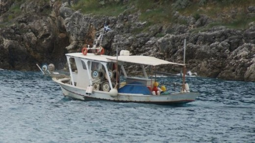 A typical Greek fishing boat heading out for the day, a bit choppy on this occasion.